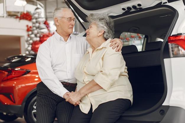 Vecchie coppie eleganti in un salone dell'automobile