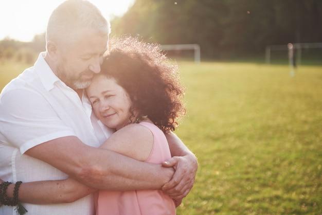 Vecchie coppie felici di estate che sorridono al parco un giorno soleggiato.