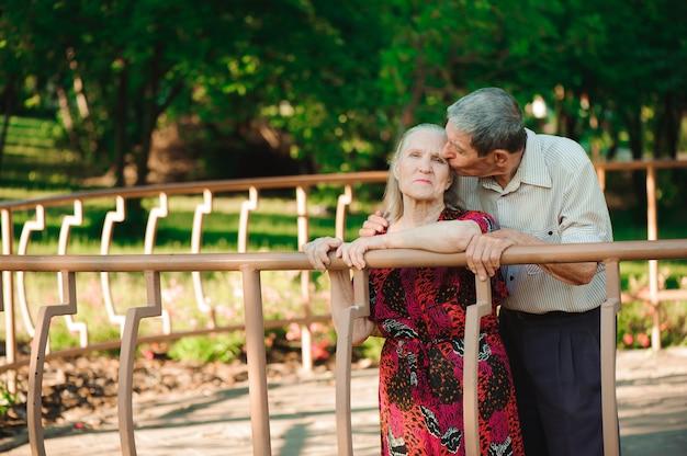 Vecchie coppie felici in un parco un giorno soleggiato.