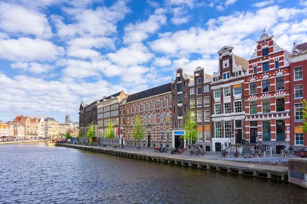 Vecchie costruzioni tradizionali variopinte nel giorno del sole a amsterdam, paesi bassi