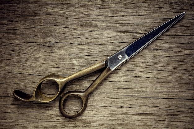 Vecchie forbici di lavoro di parrucchiere su fondo di legno