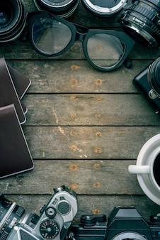 Vecchie macchine fotografiche e lente sul tavolo di legno