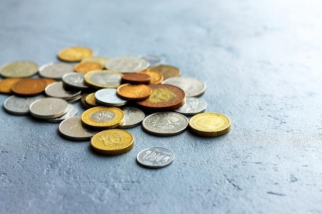 Vecchie monete di diversi paesi su uno sfondo grigio cemento.