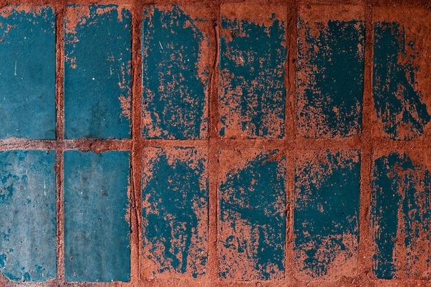 Vecchie piastrelle blu-rosse sul muro