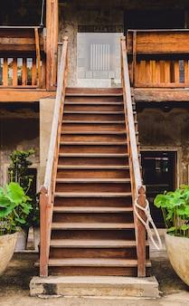 Vecchie scale di legno all'aperto con l'inferriata della scala