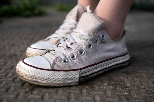 Vecchie scarpe da ginnastica bianche sulla strada