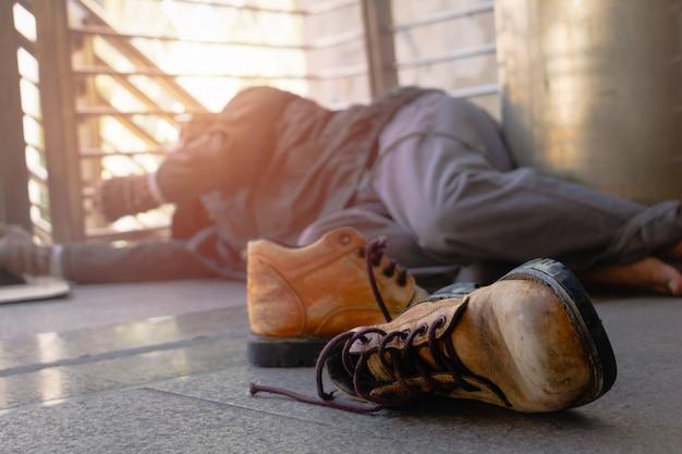 Vecchie scarpe e senzatetto il senzatetto è sdraiato sulla passerella in città.