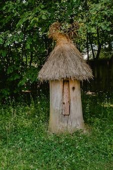 Vecchio alveare in legno con tetto di paglia