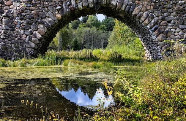 Vecchio arco del ponte di pietra con un riflesso del cielo