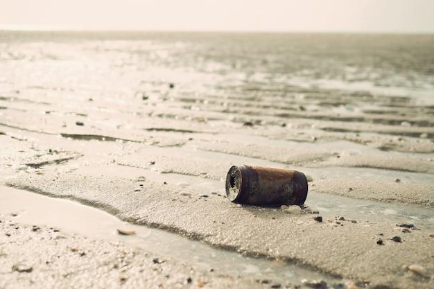 Vecchio barattolo di latta sulla spiaggia, mare sporco, riciclare, lattina di ruggine