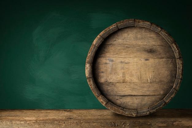 Vecchio barilotto di birra di legno sui precedenti scuri.