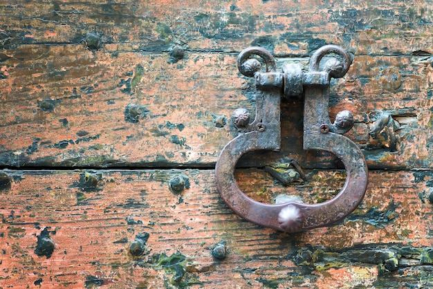 Vecchio battitore della maniglia di porta del metallo su un fondo di legno ruvido