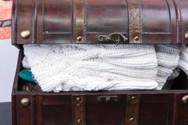 Vecchio baule con cose di vestiti a maglia