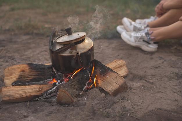 Vecchio bollitore di ferro si trova sul legno che brucia, campeggio