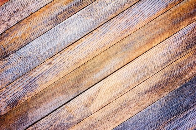Vecchio bordo di granaio grigio di struttura del fondo con le stecche di legno diagonali