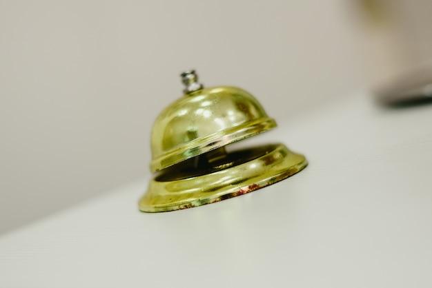 Vecchio campanello per chiamare il fattorino in un albergo, servizio campana hotel d'oro.