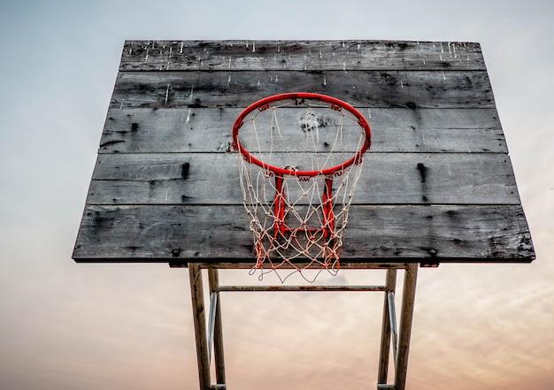 Vecchio cerchio di pallacanestro del tabellone sul tramonto del cielo