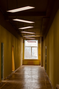 Vecchio corridoio dei tempi dell'urss con pareti gialle squallide, finestra in legno e linoleum
