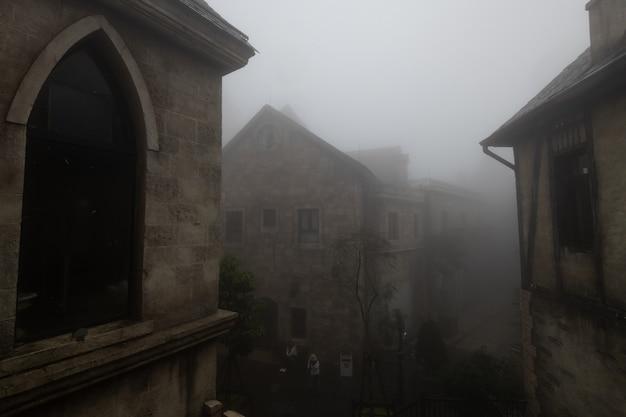 Vecchio edificio nel villaggio nella nebbia