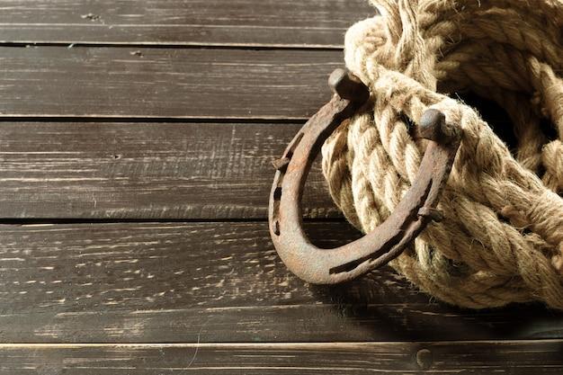 Vecchio ferro di cavallo e corda su tavole di legno