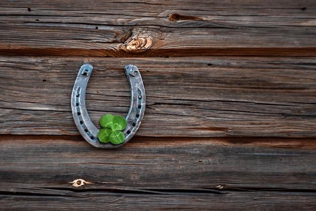 Vecchio ferro di cavallo e quadrifoglio su una tavola di legno d'epoca.