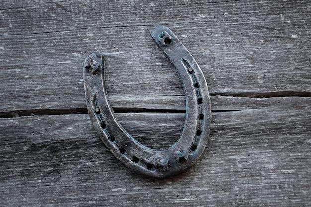 Vecchio ferro di cavallo su una vecchia tavola di legno