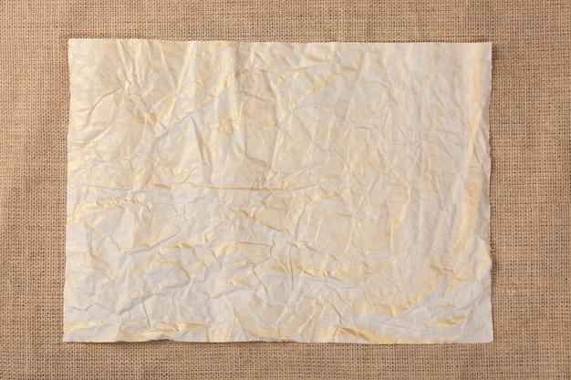 Vecchio foglio di carta stropicciata su tela di sacco.