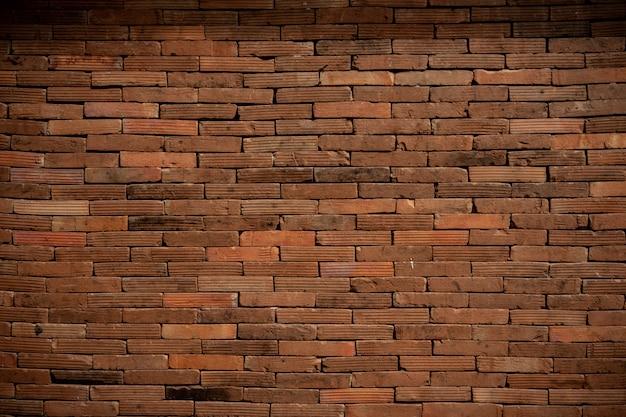 Vecchio fondo del muro di mattoni fiocamente acceso