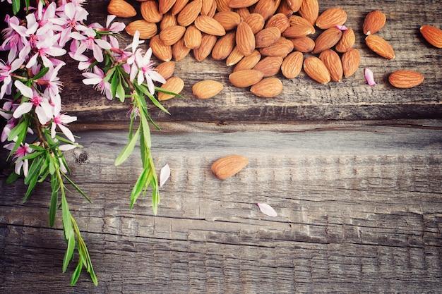 Vecchio fondo di legno con mandorle e fiori sbriciolati