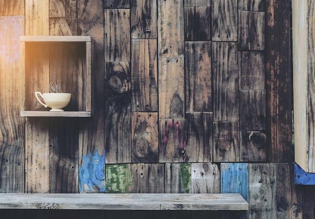 Vecchio fondo di legno della parete con gli scaffali e la vecchia tazza di caffè