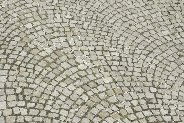 Vecchio fondo di pietra grigio della pavimentazione