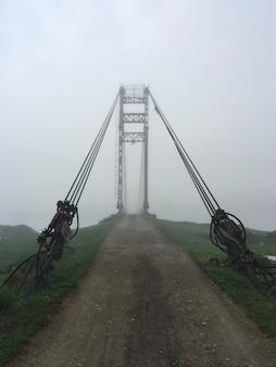 Vecchio ingresso del ponte sospeso alla nebbia. ponte del villaggio di altai. mattina presto nebbiosa