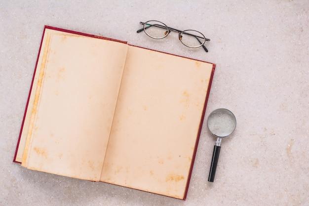 Vecchio libro aperto, lente d'ingrandimento e occhiali da vista sulla tavola di marmo bianca, vista superiore