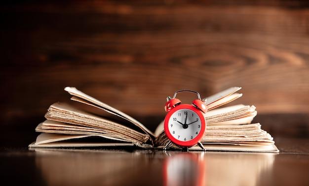 Vecchio libro e piccola sveglia sulla tavola di legno