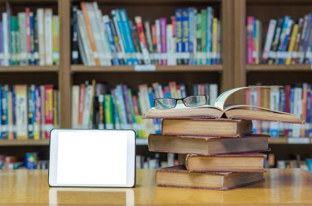 Vecchio libro sulla scrivania in biblioteca con tablet e occhiali