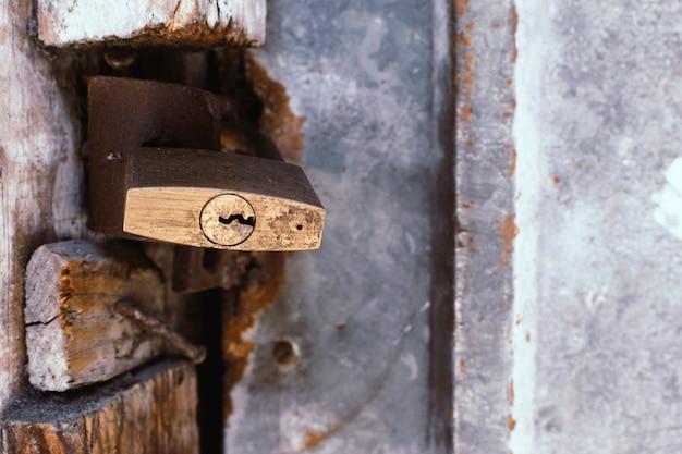 Vecchio lucchetto rustico su una vecchia porta di ferro arrugginito. spazio per copiare il testo