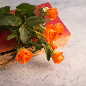 Vecchio mazzo di fiori e libro su superficie squallida