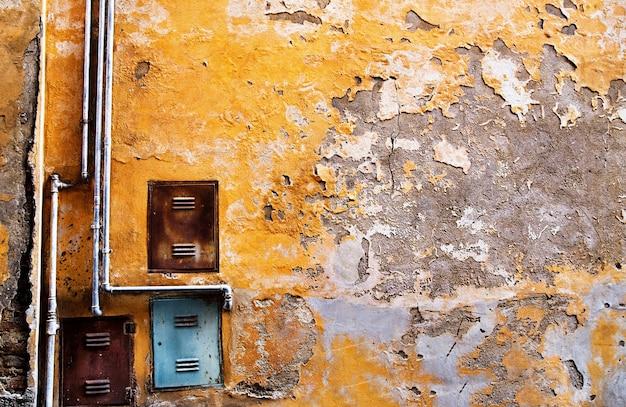 Vecchio muro di cemento con tubo di ferro
