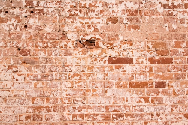 Vecchio muro di mattoni arancione con le crepe sui mattoni. squallido muro vintage