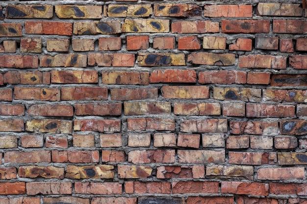 Vecchio muro di mattoni lacero e fatiscente con macchie e crepe sporche.