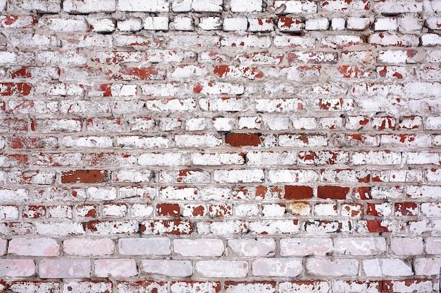 Vecchio muro di mattoni sporchi con intonaco scrostato