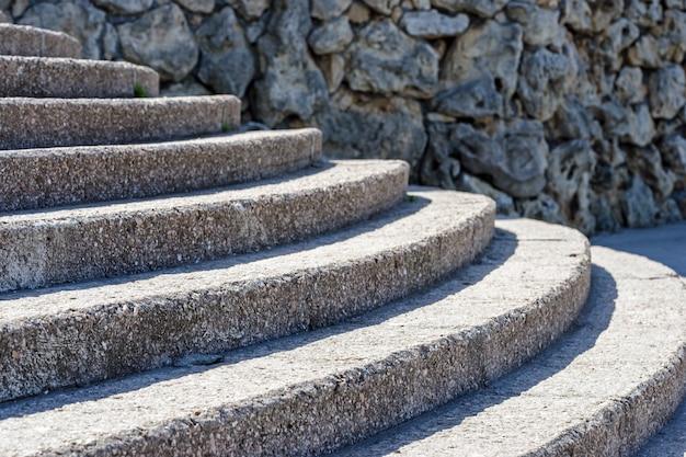 Vecchio muro di pietra e scale semicircolari in cemento