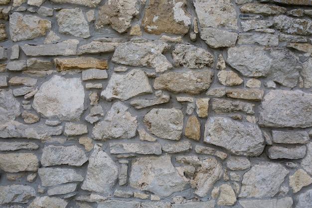 Vecchio muro fatto di grandi pietre e mattoni rotti. priorità bassa di superficie di blocchi grezzi dell'annata