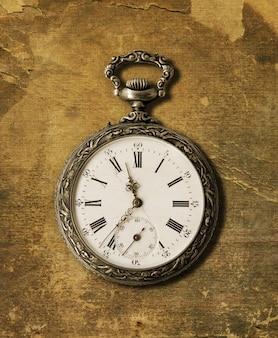 Vecchio orologio da tasca del 1900 su uno sfondo con texture