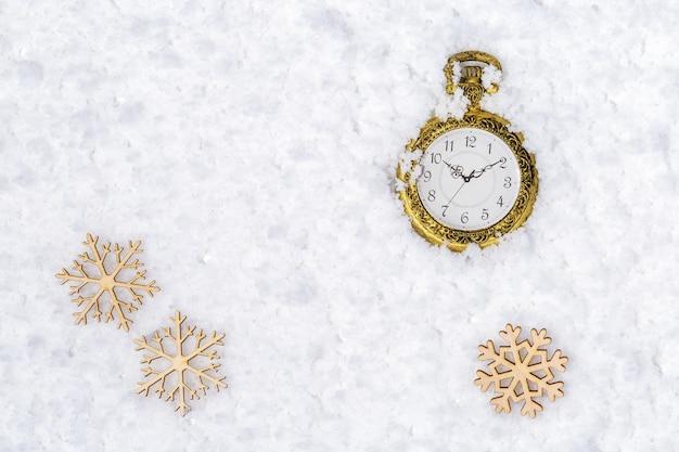Vecchio orologio da tasca e fiocchi di neve di natale sulla neve