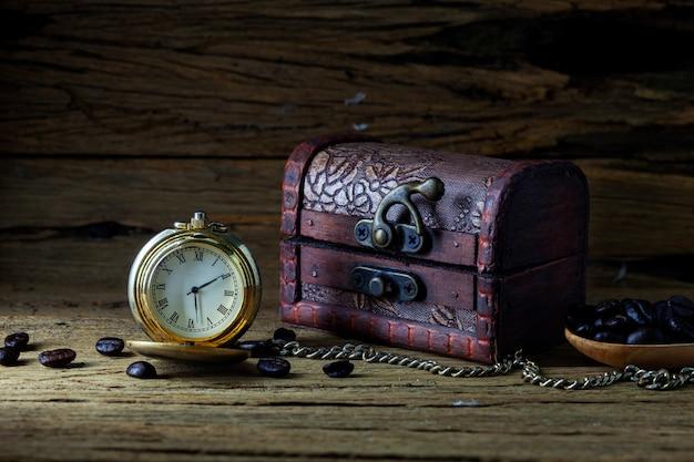 Vecchio orologio da tasca e scrigno del tesoro su legno scuro, natura morta