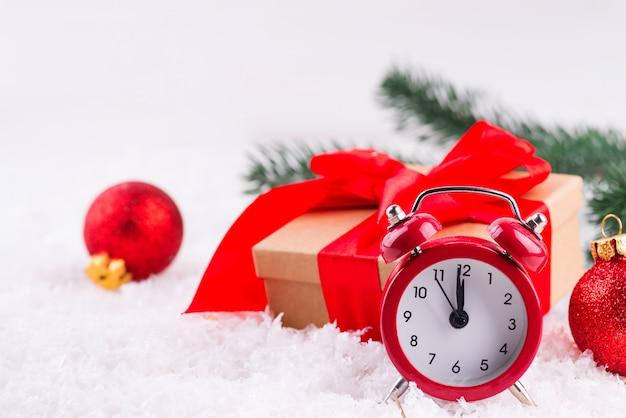 Vecchio orologio rosso con le palle rosse, contenitore di regalo marrone con un grande arco rosso che sta nella neve fresca