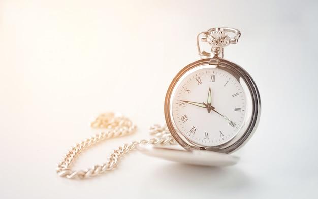 Vecchio orologio vintage su una catena su uno sfondo bianco