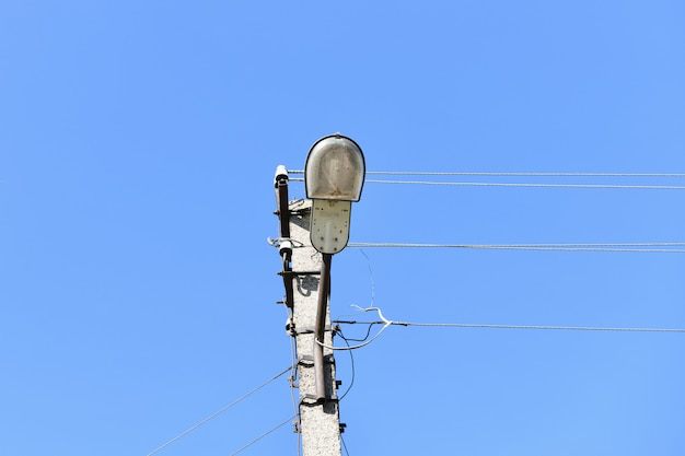 Vecchio palo elettrico concreto per la trasmissione di elettricità cablata con lampione su uno sfondo di un cielo blu nuvoloso. obsolete me. thod di fornitura di energia elettrica
