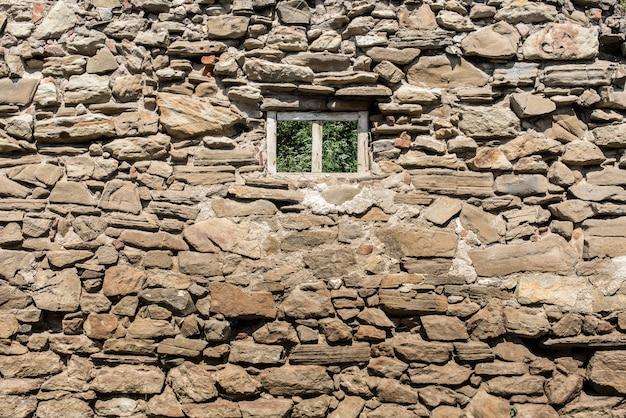 Vecchio particolare della casa con la parte anteriore della parete di pietra naturale isolata su bianco. facciata della casa